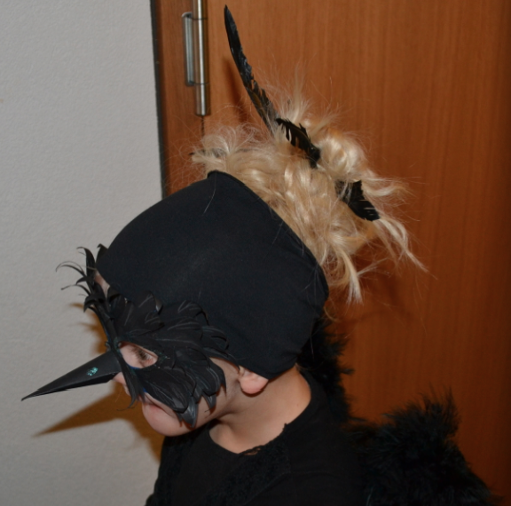 Messy bun with feathers for a crow costume at halloween